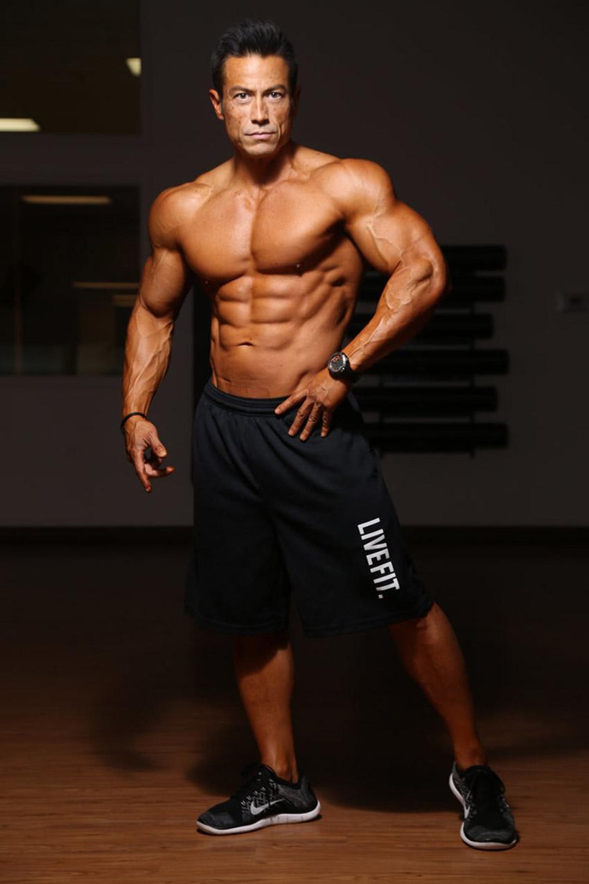 Alex Woodson posing in black shorts flexing abs