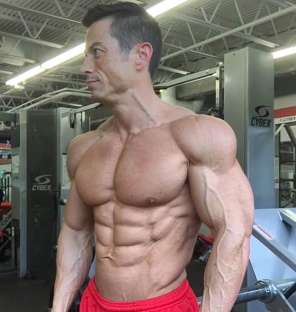 Alex Woodson in red shorts bulging muscles, vascular arms