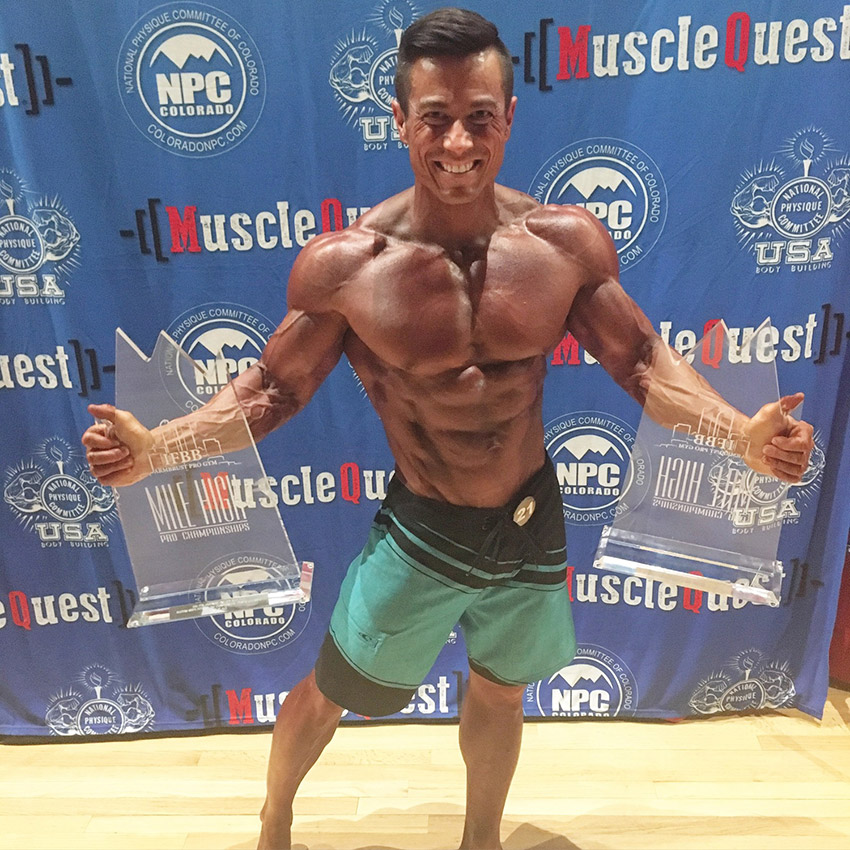Alex Woodson winning competition holding two trophies