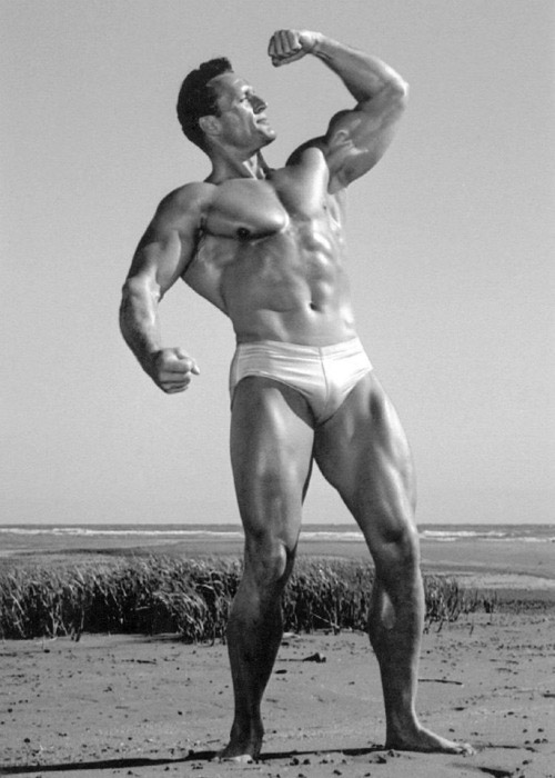 Clarence Ross on the beach posing flexing with bicep looking towards the sky in swimming shorts