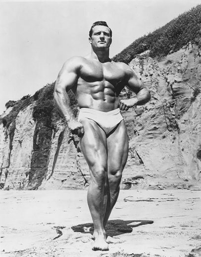 Clarence Ross on the beach posing in swimming shorts