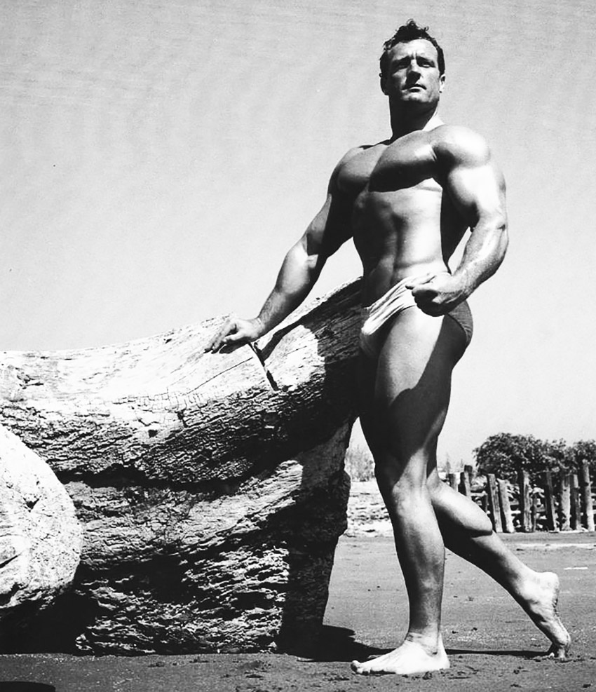 Clarence Ross standing next to a rock on the beach in swimming shorts with strong muscles