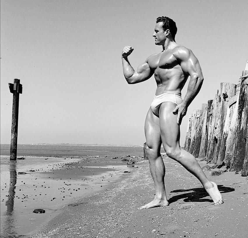 Clarence Ross on the beach posing flexing bicep and forearms