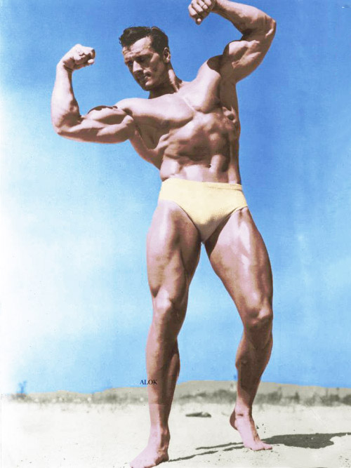 Clarence Ross photograph in colour in swimming shorts on beach flexing both biceps
