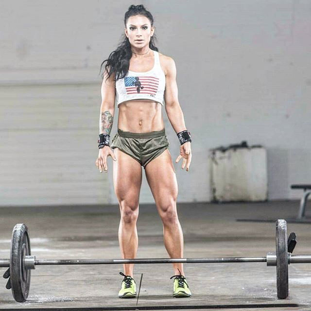 Ashley Horner standing the the gym in front of a barbell with weights attached ready to exercise