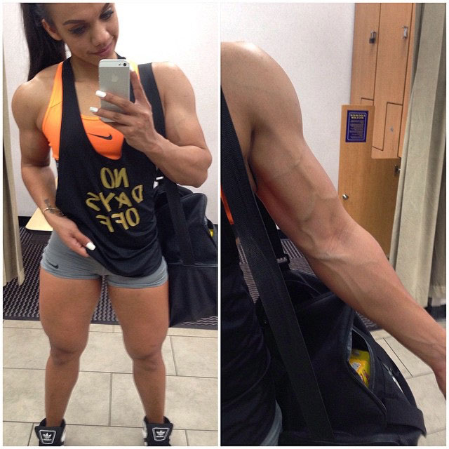 Nadia Amy flexing her right bicep and standing in short shorts also flexing her large quads