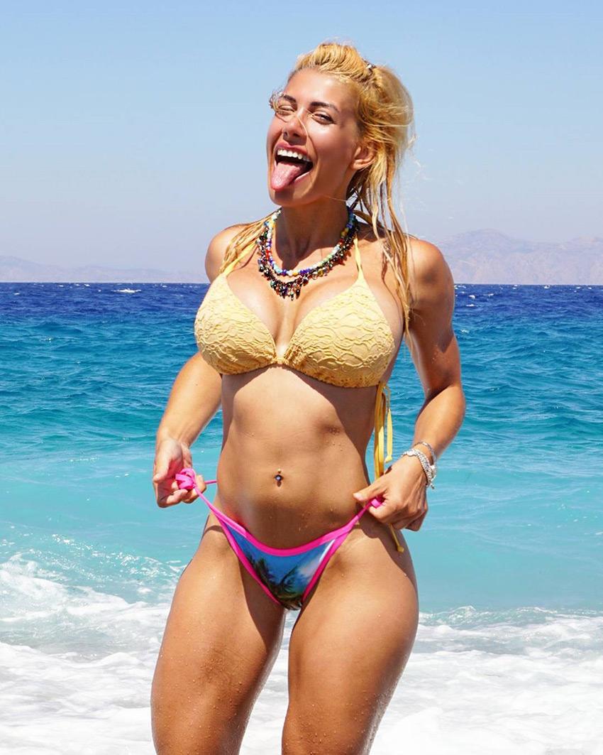 Femme Felis on a beach looking lean
