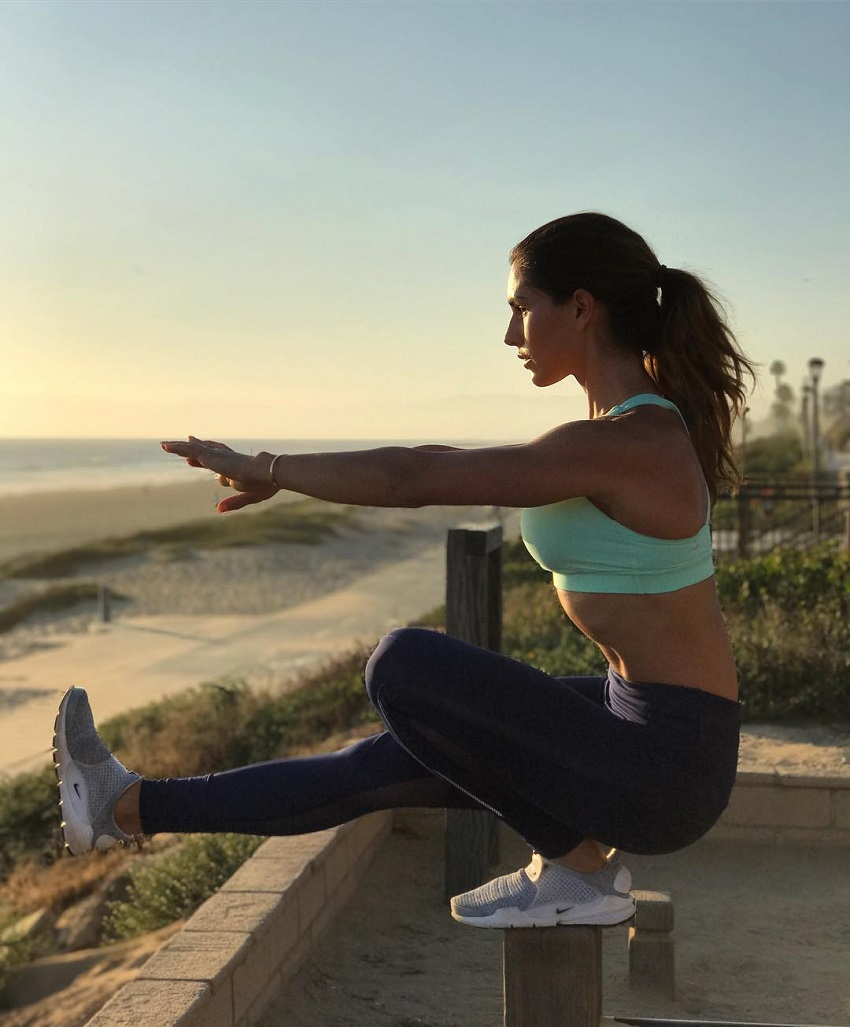Alexia Clark doing single-leg squats outdoors looking lean and healthy