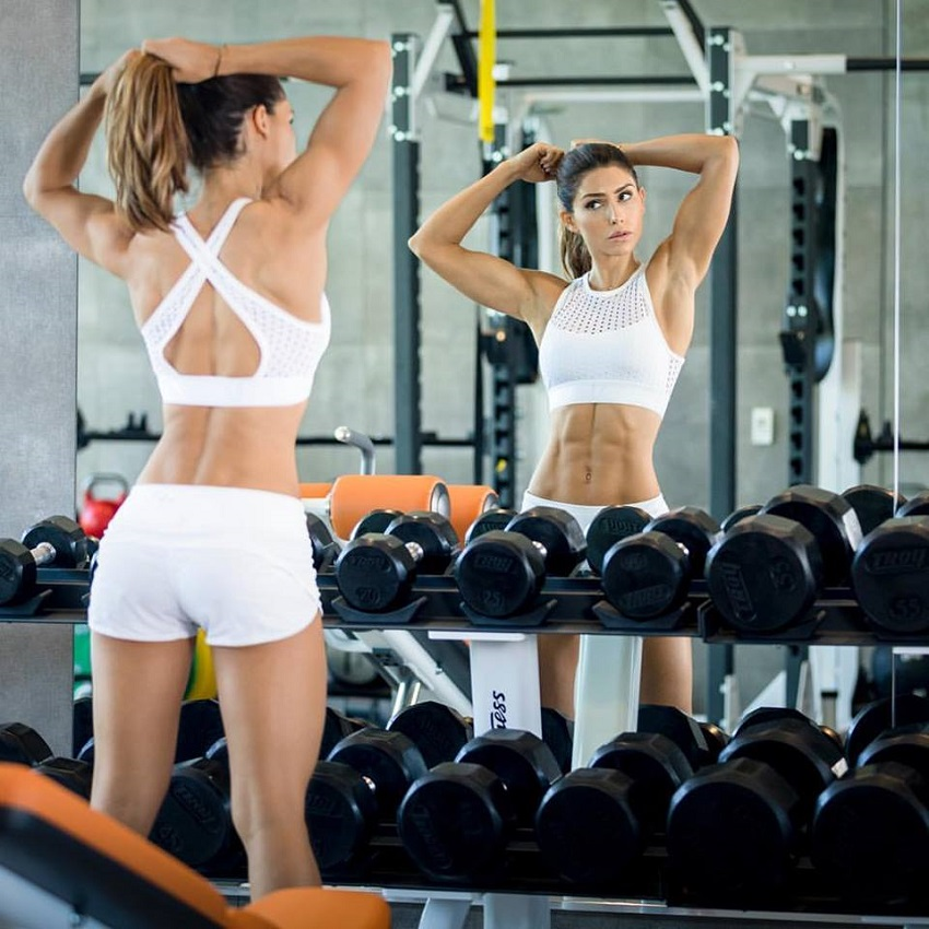Alexia Clark looking at herself in the mirror next to weights looking fit and lean