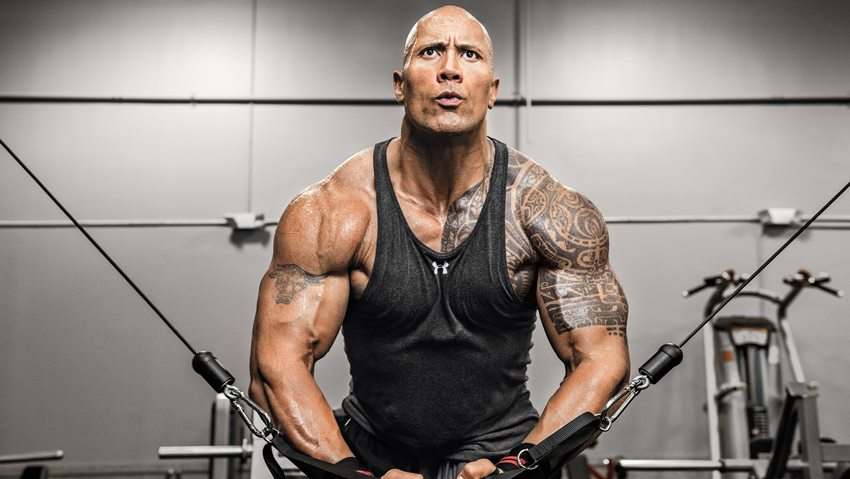 Dwayne Johnson The Rock doing cable crossovers for chets in the gym