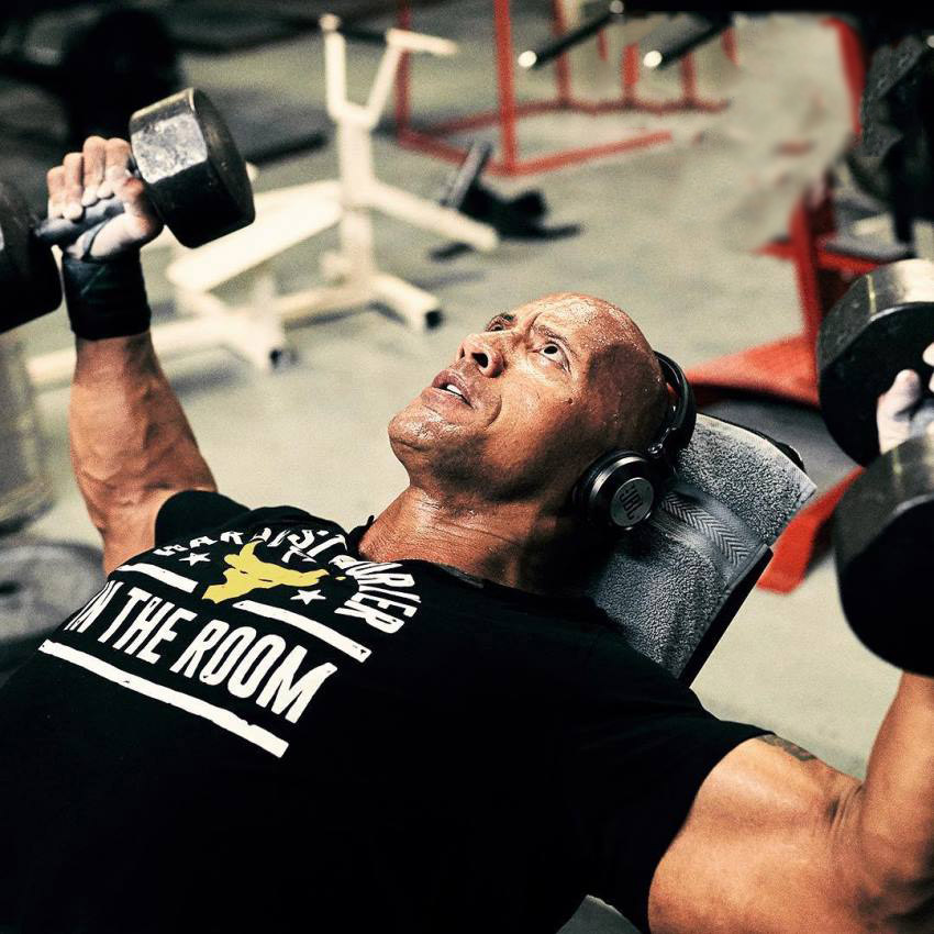 Dwayne Johnson The Rock fully focused on doing incline dumbbell flys in the gym