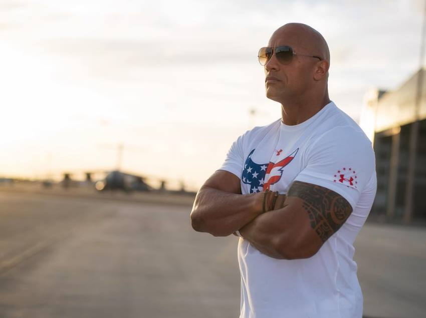 Dwayne Johnson The Rock on the beach with sunglasses with white t-shirt