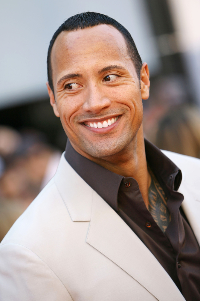 Dwayne Johnson The Rock in a white suit smiling