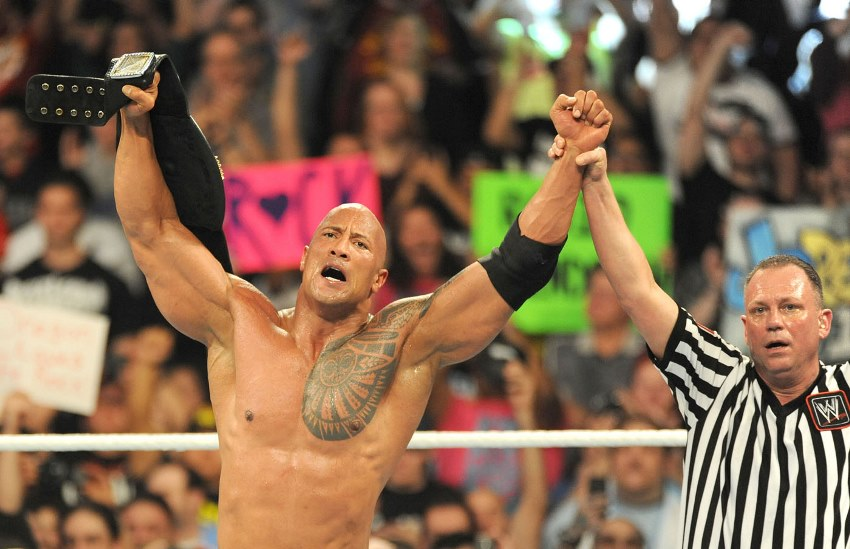 Dwayne Johnson The Rock in the ring with the judge holding his hand and proclaiming him the winner