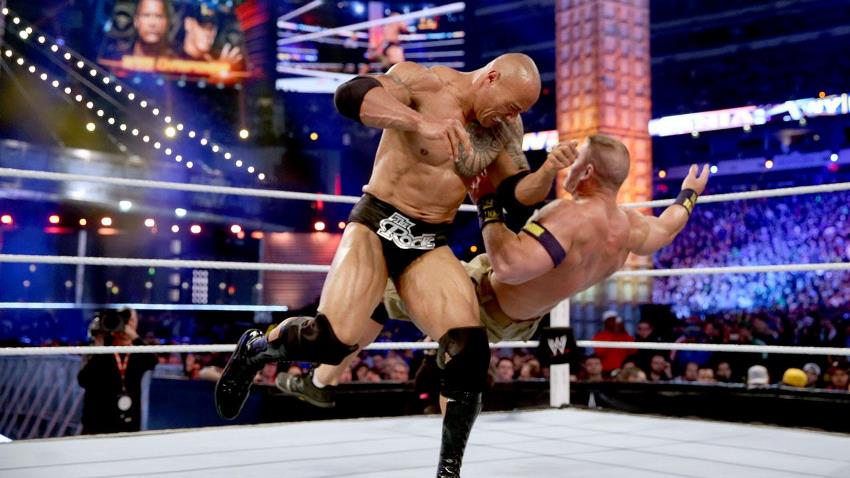 Dwayne Johnson The Rock performing a finishing move on John Cena