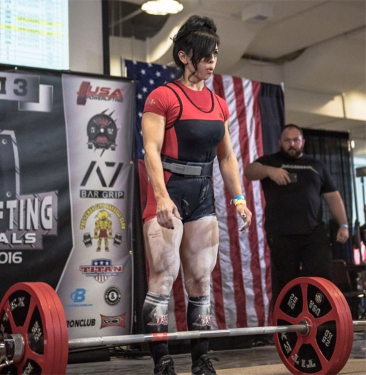 Marisa Inda Standing in front of the barbell in a power lifting competition ready to take the weight