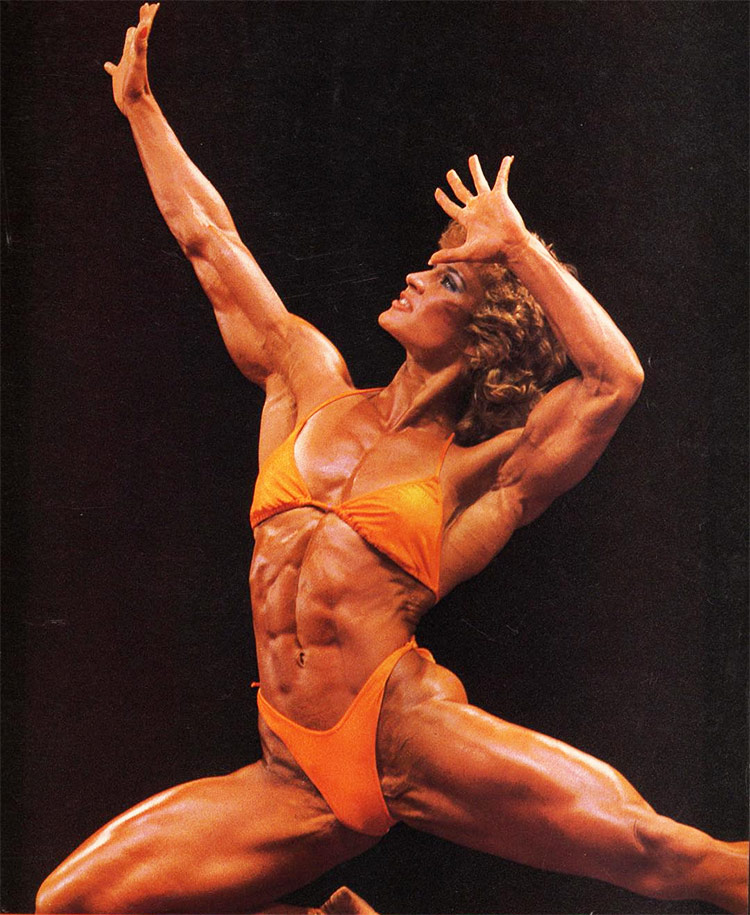 Corinna Everson posing on stage during a routine for a fitness competition.