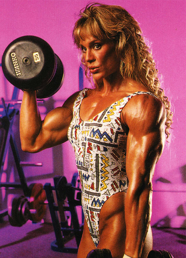 Corinna Everson lifting weights in the gym, displaying her muscular arms.
