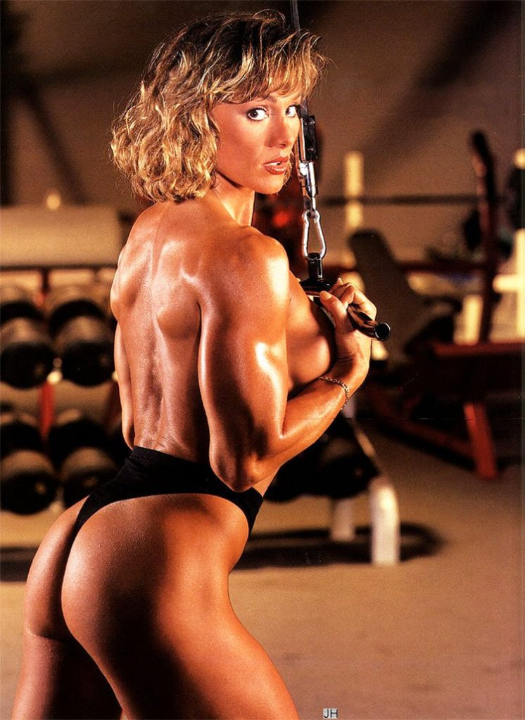 Corrina Everson showing her glutes while pulling a weight on a rope.