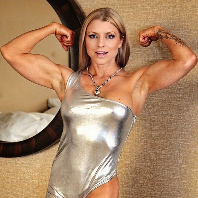 Fawnia Mondey wearing a silver dress flexing both biceps looking strong and lean