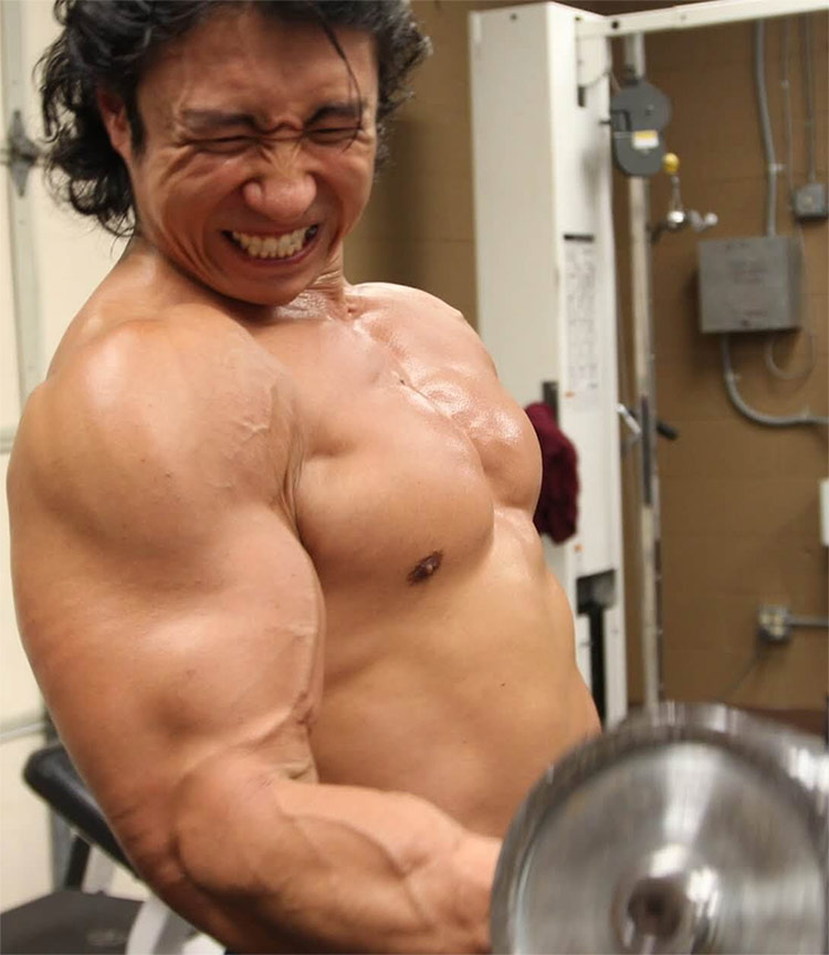 Mike Chang showing everyone the correct form for bicep curls, displaying his huge arms for everyone to see.