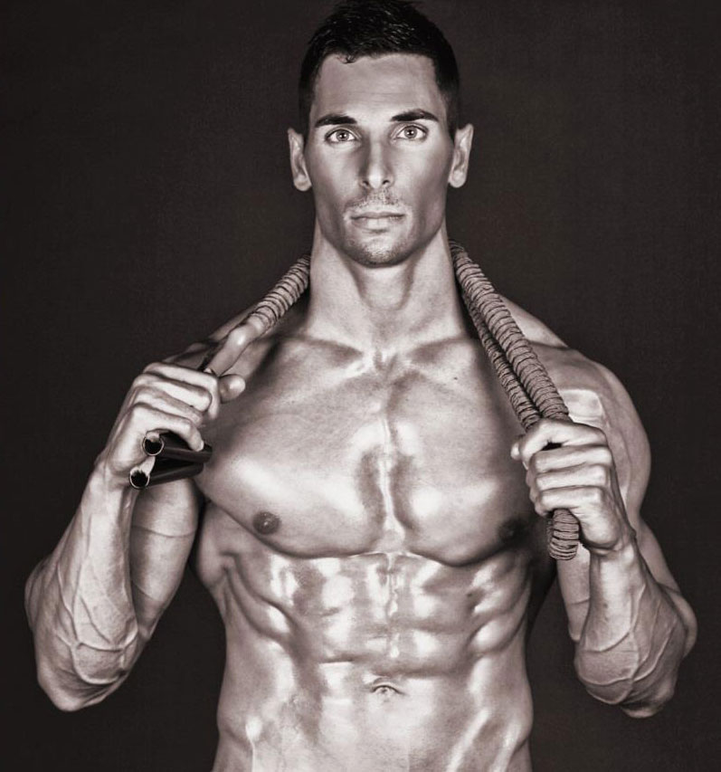 Mike Raso standing with shirt off with ripped abs holding towel around the back of his neck