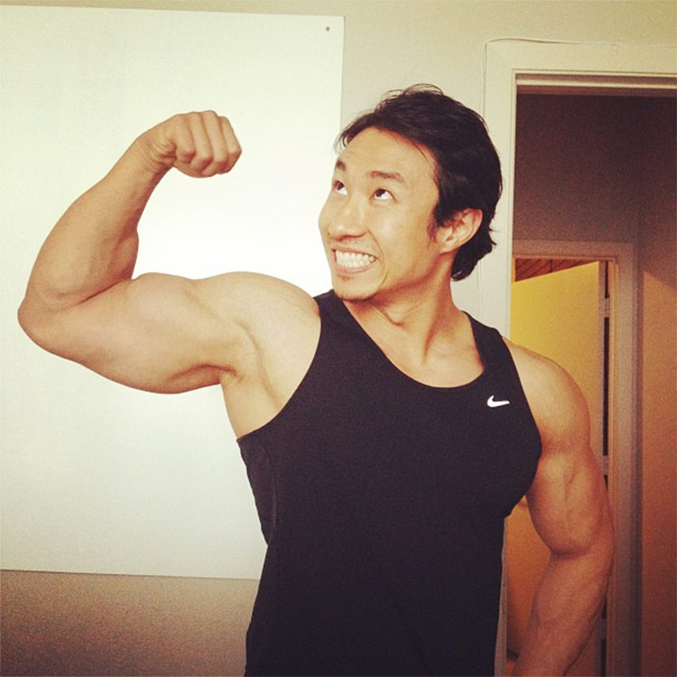 Mike Chang flexing his biceps looking very happy.