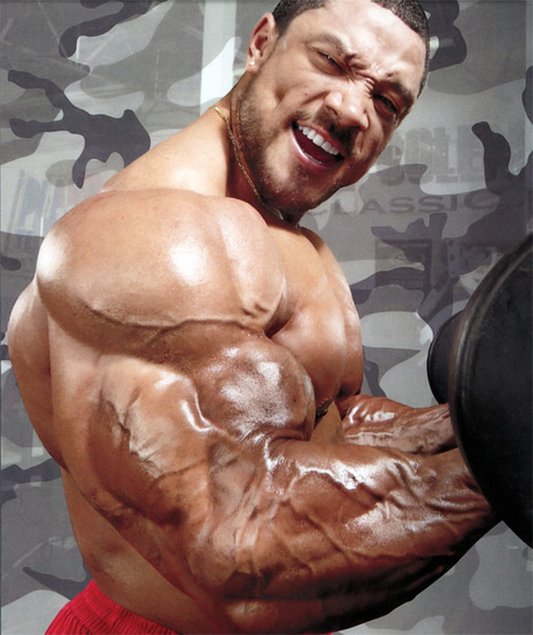 Roelly WInklaar flexing his arms, showing the muscular definition on his biceps and triceps.