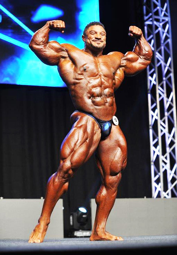 Roelly Winklaar posing on stage during a fitness competition.