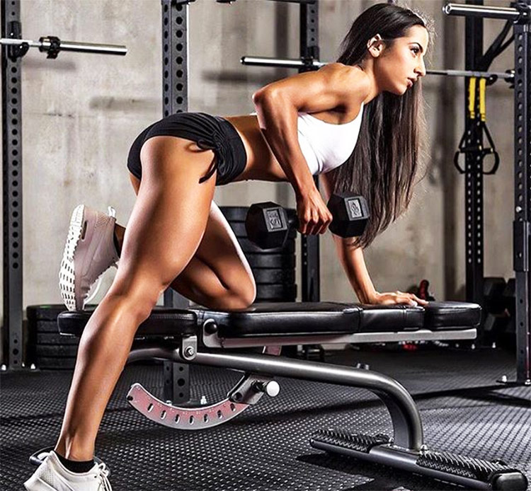 Sarah Ramadan training in the gym, being photographed while holding a dumbbell.
