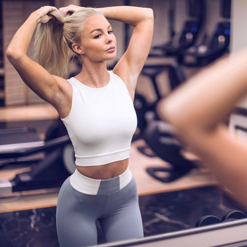 Alexandra Bring in a sportswear with both of her hands in her hair, looking at herself in a gym mirror