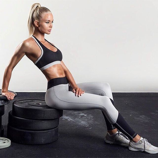 Alexandra bring sitting on weight plates, while doing a photoshoot, looking sideways