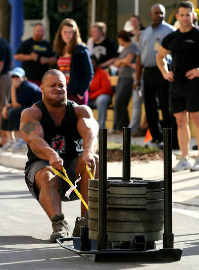 elliott hulse drags a weighted trolley in a strongman competition