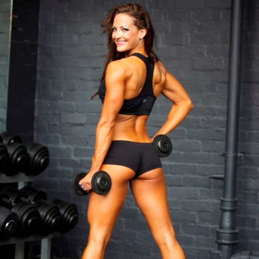 Erin Stern posing in sportswear with two dumbbells showing her back and glutes