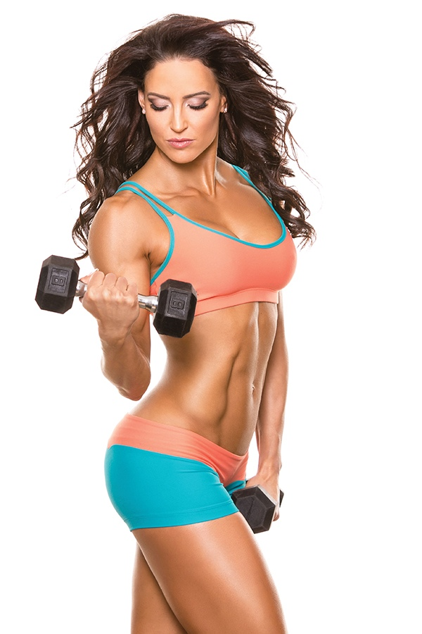 Erin Stern lifting a dumbbell while seriously looking at it - showing her fit abs and body from a side pose