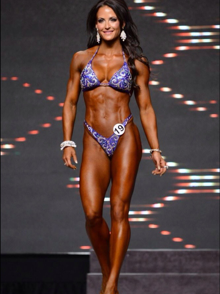 Erin Stern walking towards judges on the stage, proudly presenting her physique and smiling