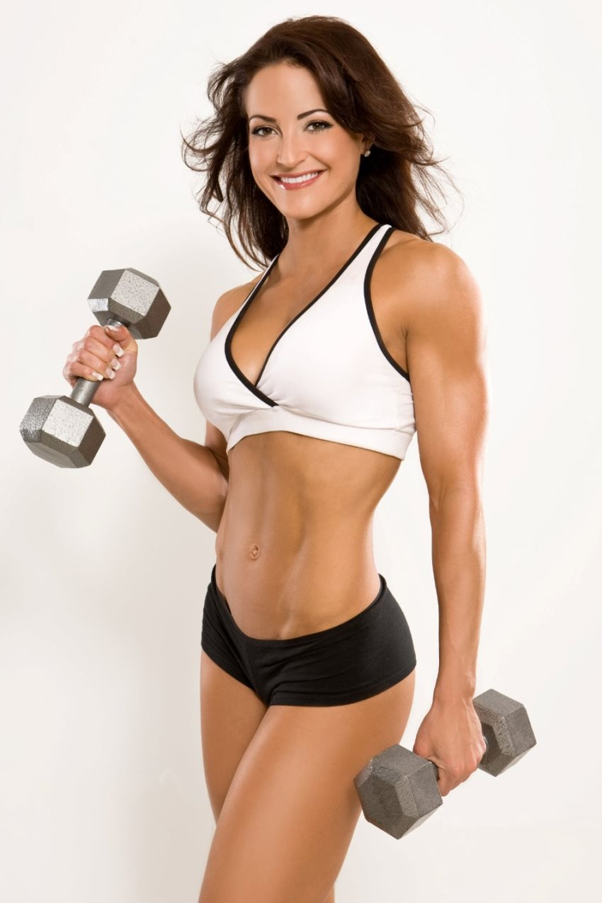 Erin Stern with two dumbbells in her hands in sportswear, smiling at the camera