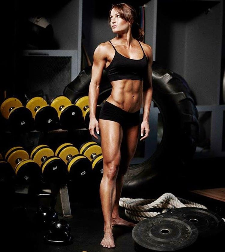 Erin Stern doing a photoshoot in the gym, looking in the distance, showing off her lean abs, arms, and legs