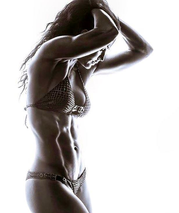 Erin Stern side show of her while posing for a photoshoot with hands in her hair, showing off her awesome abs
