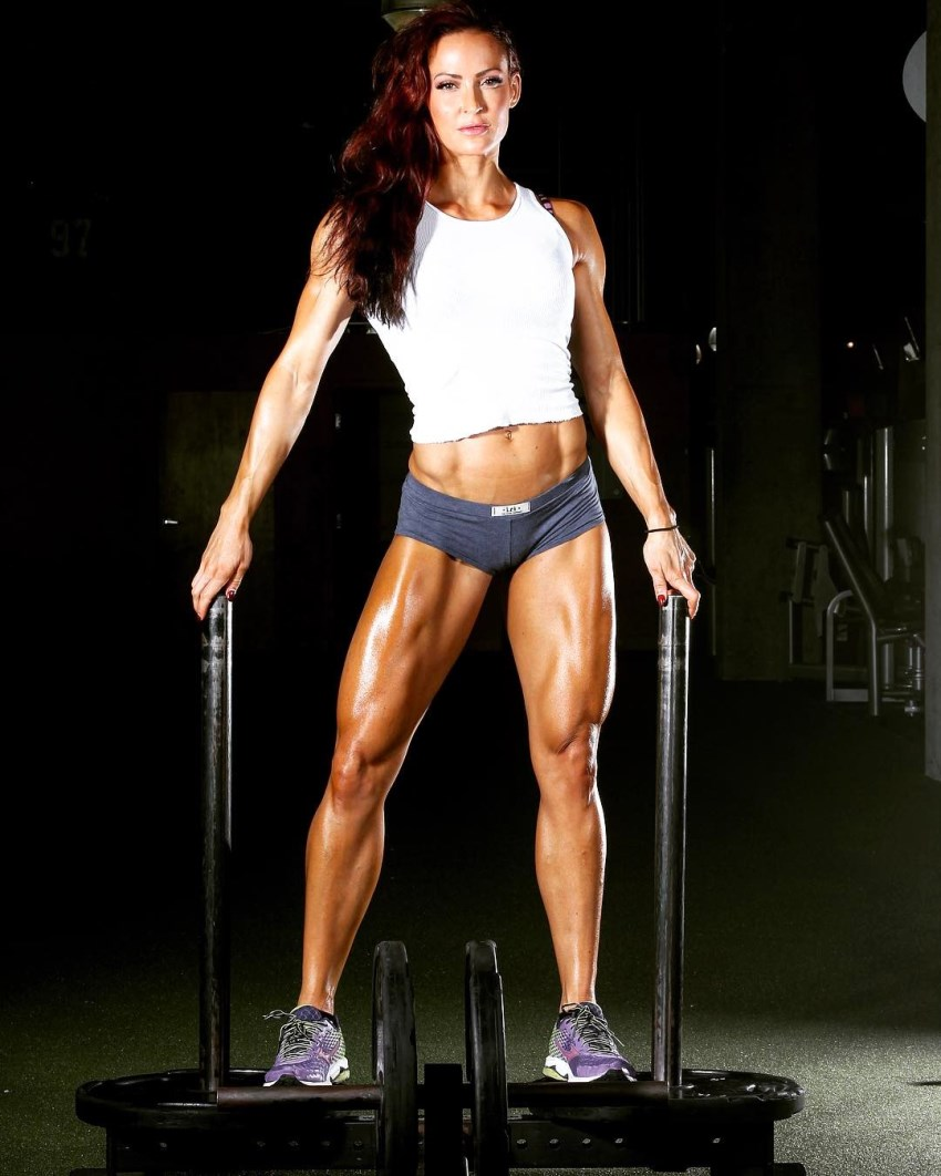 Erin Stern looking seriously at the camera, standing on two weight plates in the gym, holding onto bars, showing her muscular legs and arms