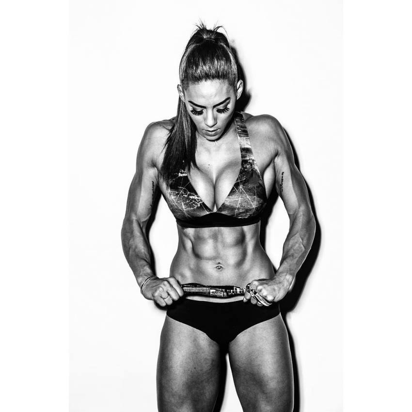 Hannah Eden during a photo shoot, showing her ripped abs, chest, arms, and legs, as she looks down with a serious expression