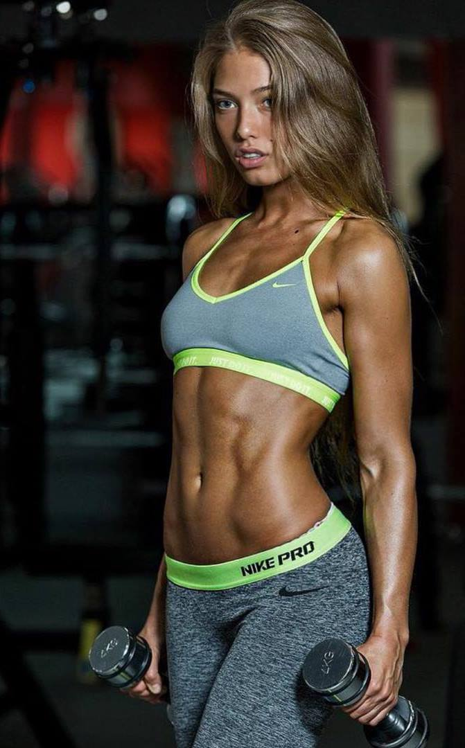 Rida Kashipova profile picture, doing a photoshoot in the gym, showing her amazing muscular and ripped arms and abs
