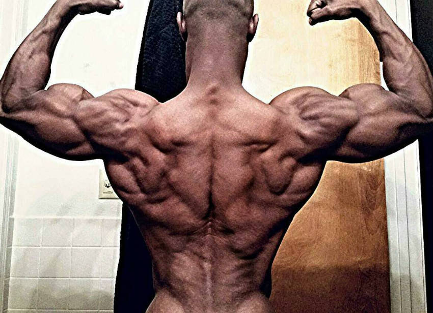 robert niter flexes his back and arm muscles