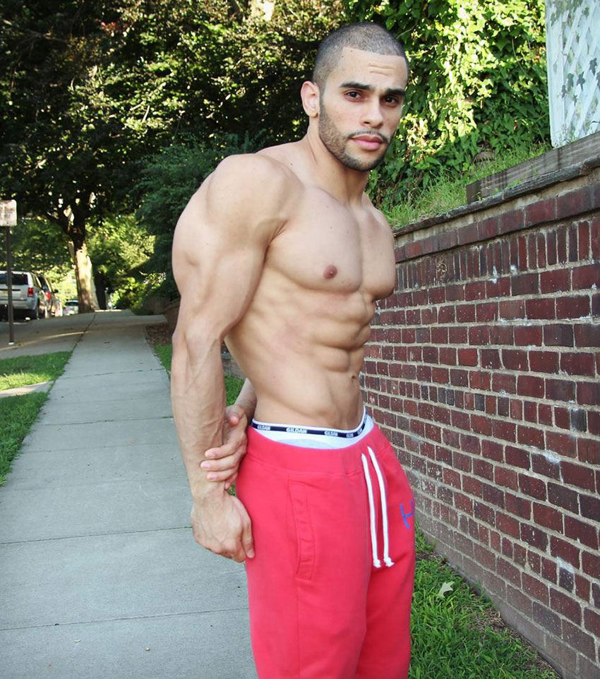 Alex Los Angeles flexing his tricep and abs with his hands behind his back in a bodybuilding pose