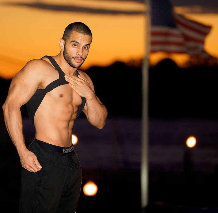 Alex Los Angeles pulling up his t-shirt shwoing his abs with an American flag in the background