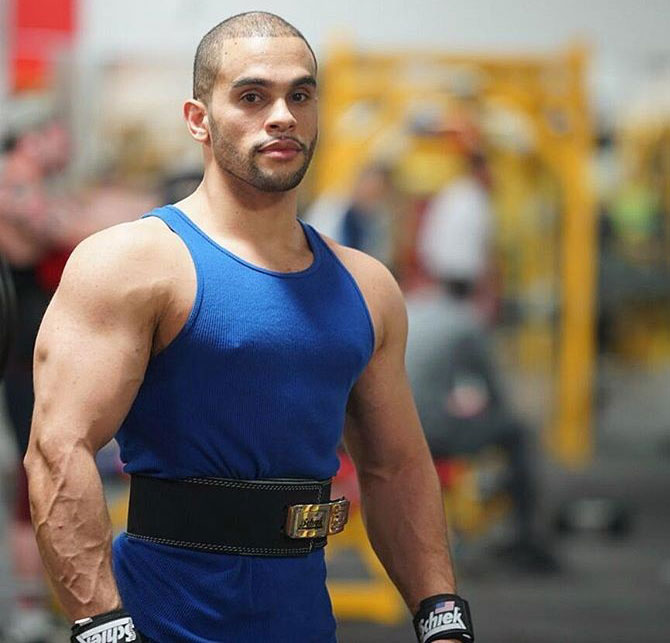 Alex Los Angeles wearing a lifting belt in the gym looking big and bulky while wearing a blue vest