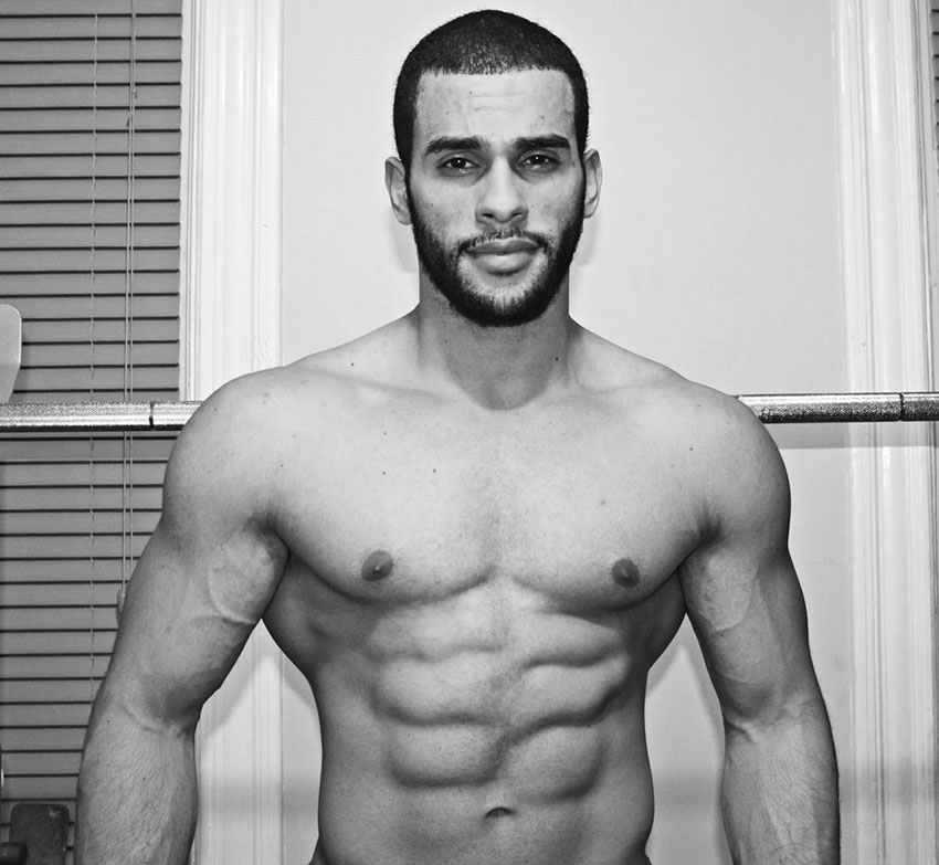 Alex Los Angeles posing in his house with his shirt off showing his ripped abs