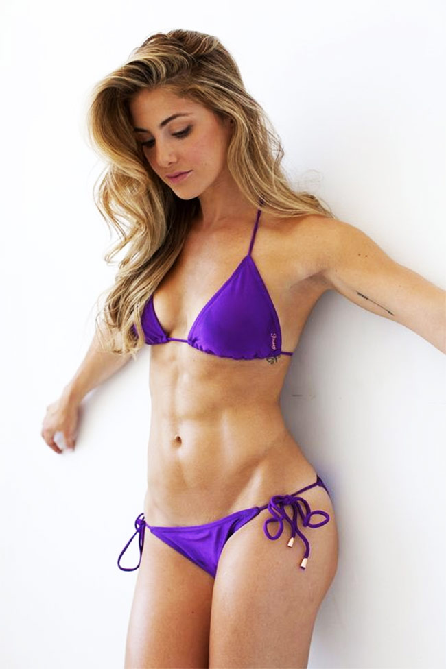 Alex Silver Fagan wearing a blue bikini in front of a white backdrop, posing as a fitness model in a professional photoshoot.