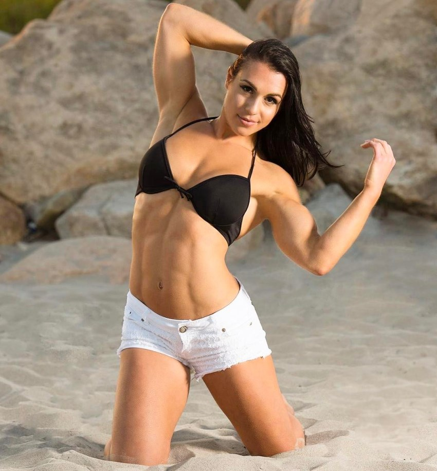 Alyssa Michelle Agostini keeling in the sand while flexing her biceps and abs