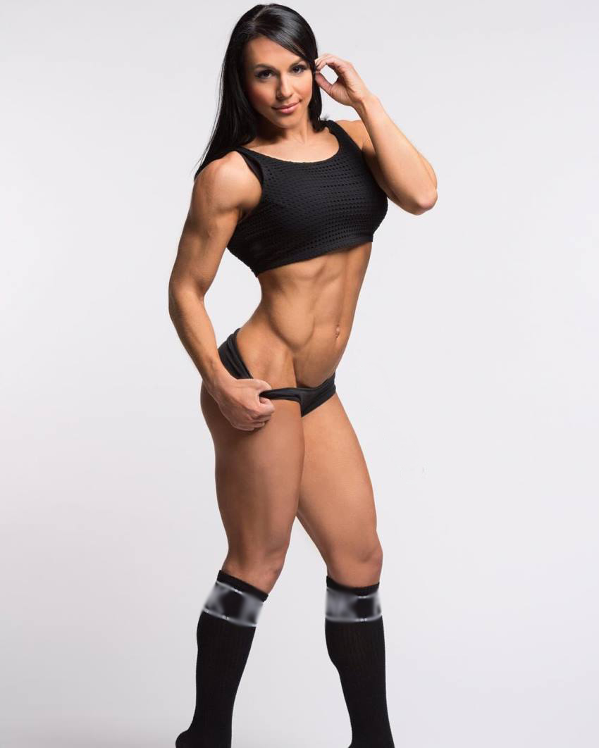 Alyssa Michelle Agostini standing for a photoshoot, revealing her ripped arms, abs, and legs from the side